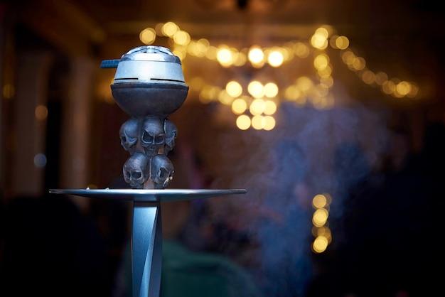 Narghilè decorato con teschi in una nuvola di fumo close-up su uno sfondo sfocato