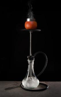 Narghilè moderno con ciotola di vetro e aroma di pompelmo su sfondo nero