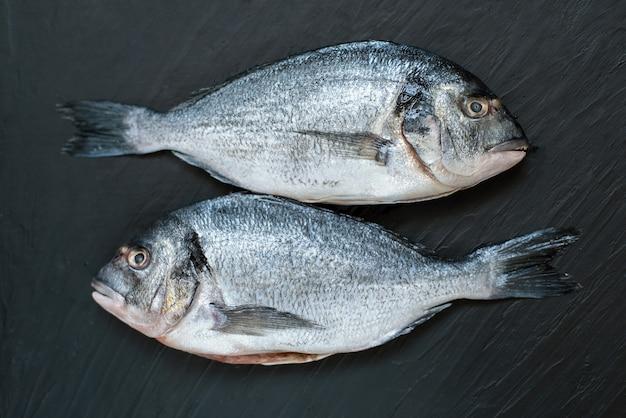 Nasello di pesce crudo. cinque filetti di pesce crudo con pomodori freschi biologici su ghiaccio su oscurità