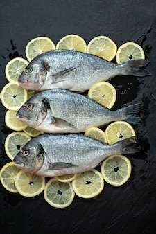 Nasello di pesce crudo. cinque filetti di pesce crudo con pomodori freschi biologici