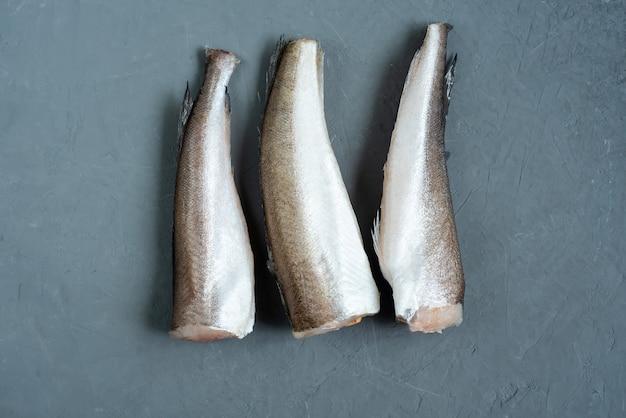 Nasello di pesce crudo. cinque filetti di pesce crudo su grigio