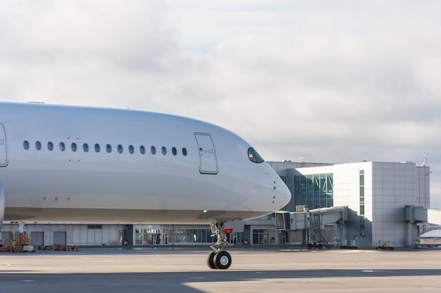 Naso e fusoliera con finestre dell'aeroplano sullo sfondo del terminal dell'aeroporto.