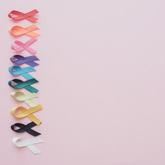 Nastri colorati su sfondo rosa, consapevolezza del cancro