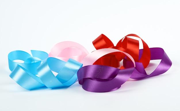 Nastri intrecciati in raso blu, rosa, rosso e viola su bianco