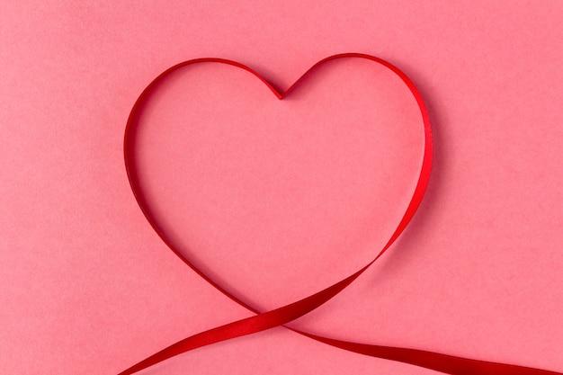 Nastro a forma di cuore su uno sfondo rosa.