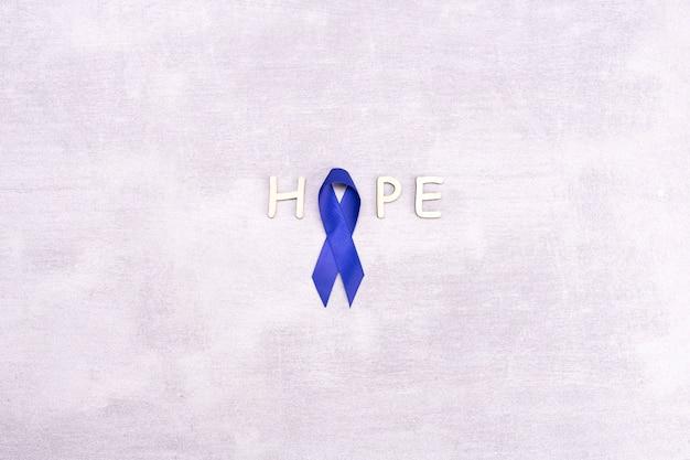 Nastro blu con la parola speranza, sfondo tonico, cancro del colon, cancro del colon-retto su un grigio
