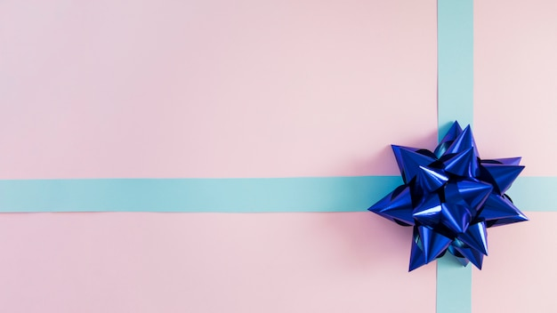 Nastro blu decorativo e fiocco su sfondo rosa