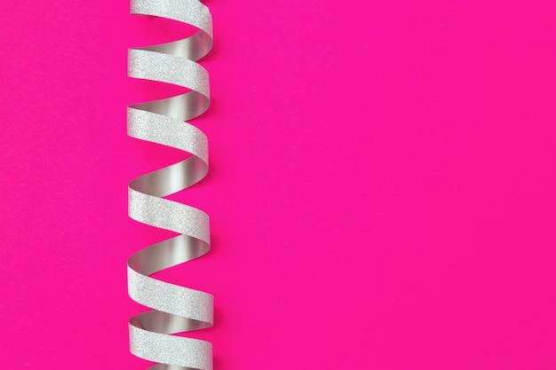 Nastro d'argento decorativo su sfondo rosa con spazio di copia. biglietto di auguri per compleanno, vacanze anniversario. buono regalo.