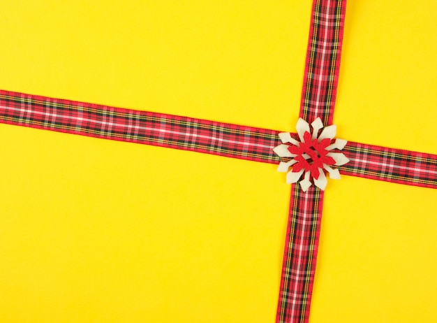 Nastro decorativo rosso in una croce di scatola su una croce