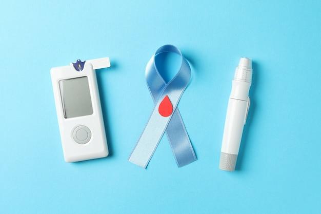 Nastro di consapevolezza blu e accessori per il diabete su sfondo blu