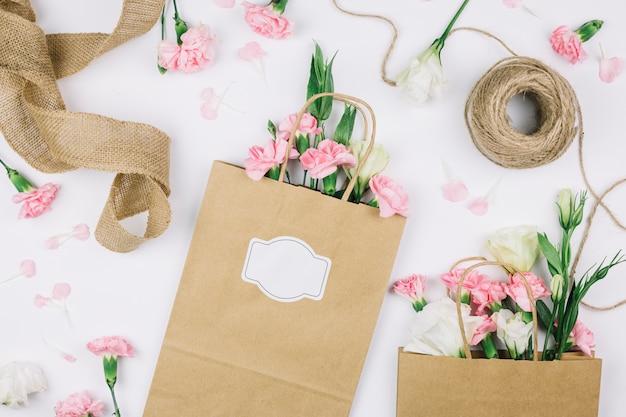 Nastro di juta; rocchetto di filo e sacchetti di carta con fiori eustoma e garofani su sfondo bianco