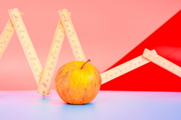 Nastro di misurazione accanto a una mela, concetto di perdita di peso con dieta sana.