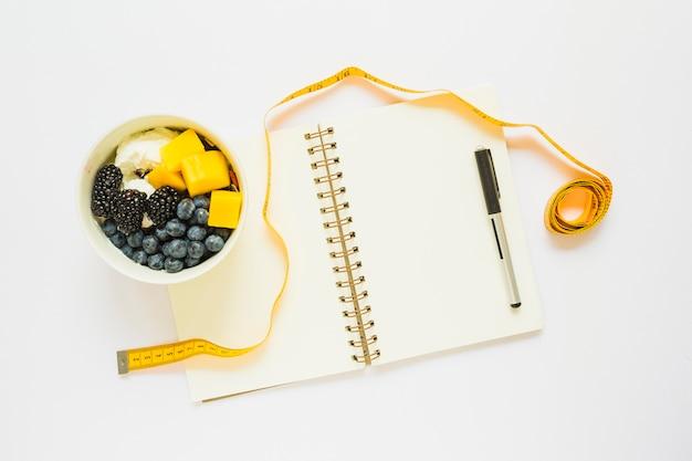 Nastro di misurazione; bicchiere di frutta con yogurt; penna e quaderno a spirale su sfondo bianco