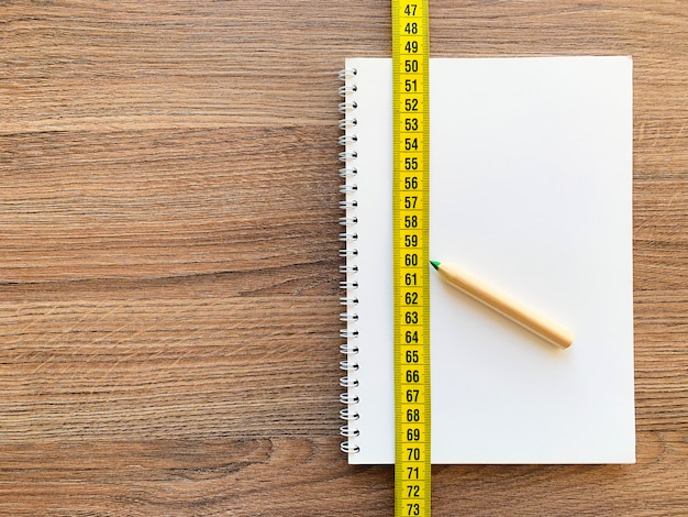 Nastro di misurazione con blocco note e penna del diario del libro per forma fisica sana