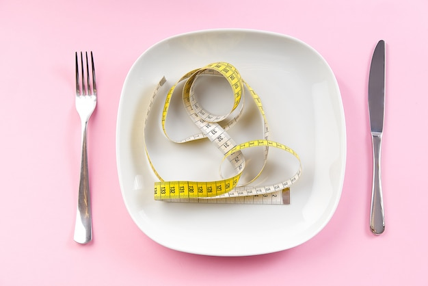 Nastro di misurazione di perdita di peso sul piatto bianco, concetto della dieta sana.