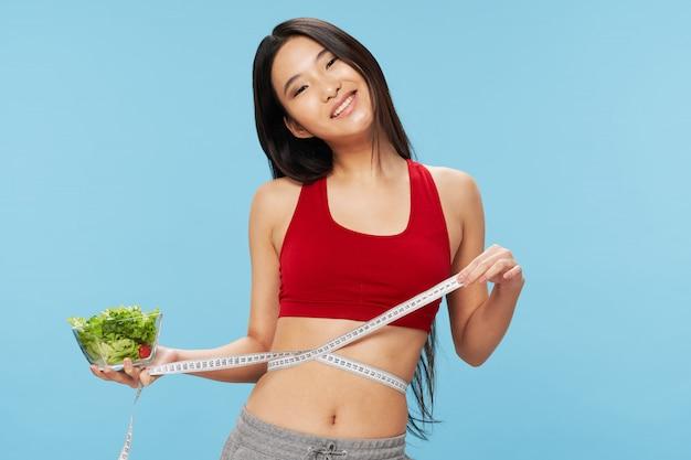 Nastro di misurazione e ciotola di insalata della tenuta asiatica della donna