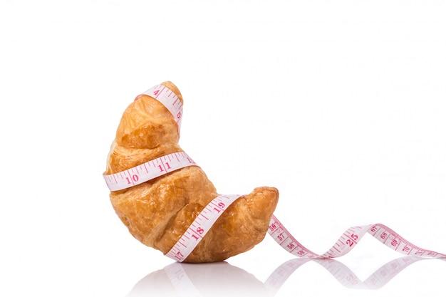 Nastro di misurazione e croissant. cibo spazzatura, obesità o concetto di cibo sano