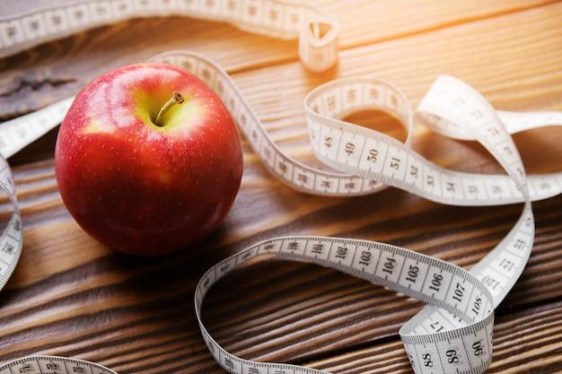 Nastro di misurazione e mela rossa. il concetto di dieta, stile di vita sano e corretta alimentazione.