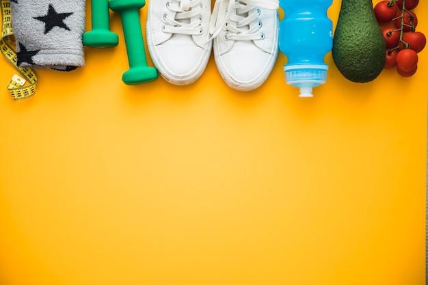 Nastro di misurazione; fascia da braccio; manubri; scarpe; bottiglia d'acqua avocado e pomodorini su sfondo giallo