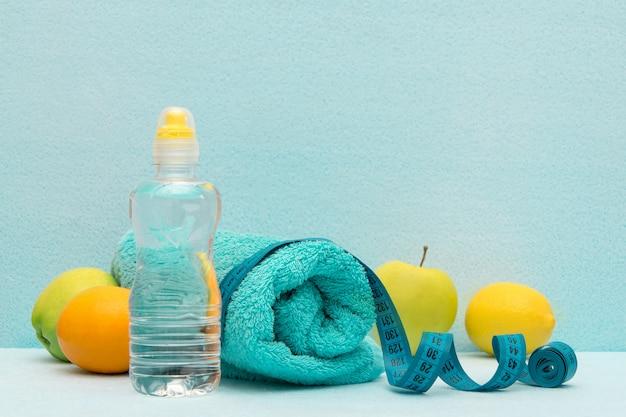 Nastro di misurazione su uno sfondo di frutta, asciugamani e una bottiglia di acqua.