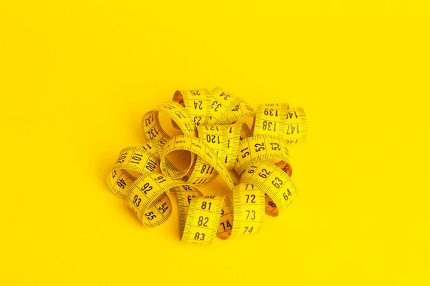 Nastro di misurazione su uno sfondo giallo. nastro di misurazione a forma di spirale attorcigliata su uno sfondo giallo. concetto di dimagrimento e dieta, copia spazio