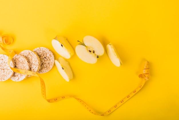 Nastro di misurazione vicino a fette di frutta e pane croccante