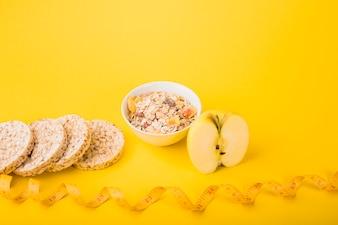 Nastro di misurazione vicino a frutta, pane fresco e ciotola di muesli