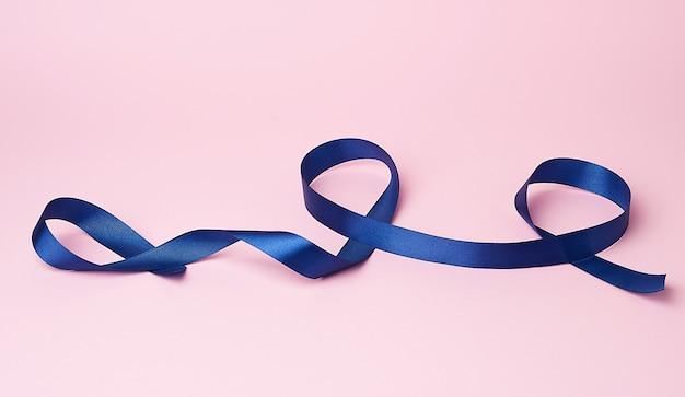 Nastro di seta blu scuro attorcigliato in anelli su una superficie rosa