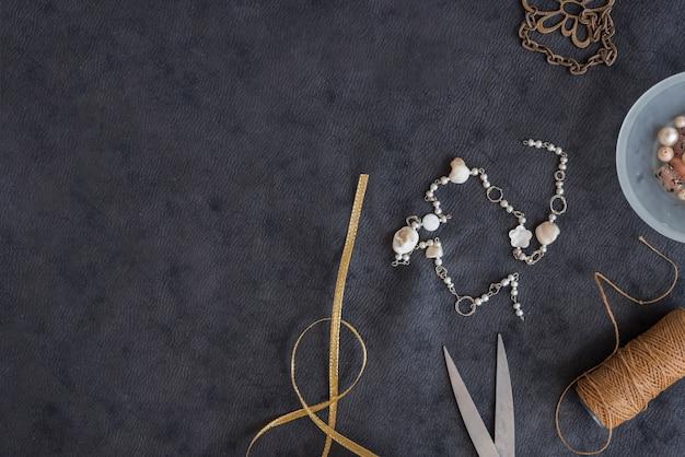 Nastro dorato; braccialetto; forbice; rocchetto di filo su sfondo nero con texture