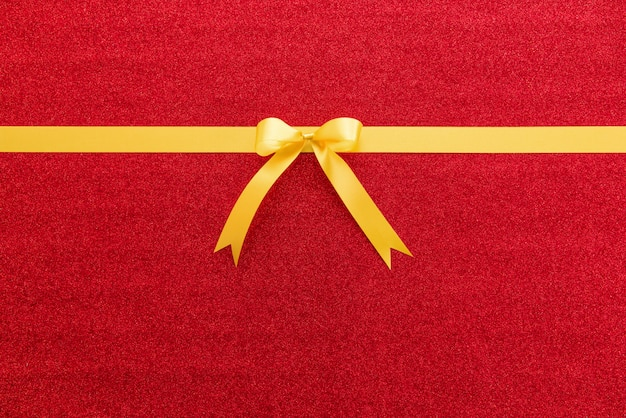 Nastro dorato di raso lucido con fiocco su sfondo colorato glitter rosso