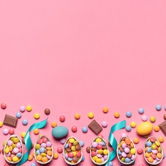 Nastro; gemme caramelle e uova di pasqua con spazio per scrivere il testo su sfondo rosa