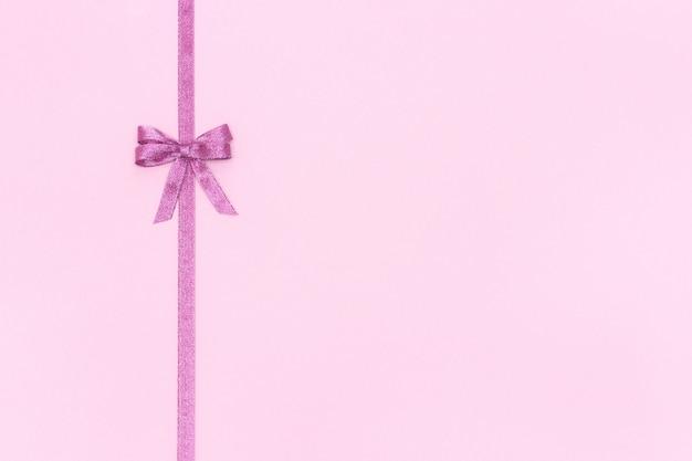 Nastro lucido decorativo con fiocco su sfondo rosa.