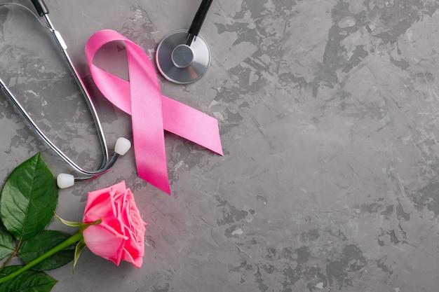 Nastro rosa, stetoscopio e rosa su uno sfondo di cemento