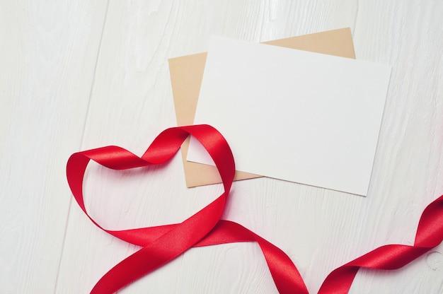 Nastro rosso a forma di cuore e biglietto di auguri vuoto foglio di carta