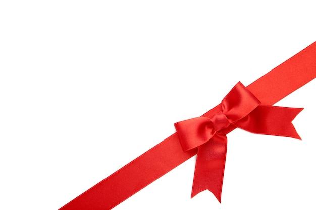 Nastro rosso con fiocco con code isolato su superficie bianca
