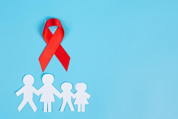 Nastro rosso di conoscenza e carta tagliata in famiglia, consapevolezza dell'hiv, giornata mondiale contro l'aids e giornata mondiale della salute sessuale.