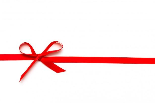 Nastro rosso o corda legata in arco isolato su sfondo bianco