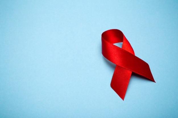 Nastro rosso su uno sfondo grigio scuro. simbolo della giornata mondiale contro l'aids o del mese della consapevolezza del cancro o dell'hiv e concetto di assistenza sanitaria. copia spazio