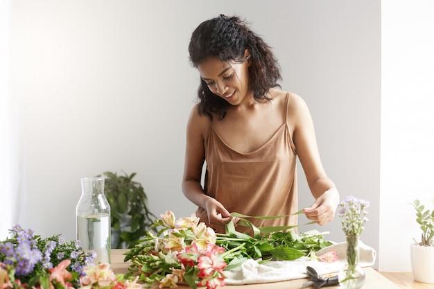 Nastro sorridente della tenuta del fiorista africano allegro della donna che lavora con i fiori sopra la parete bianca.