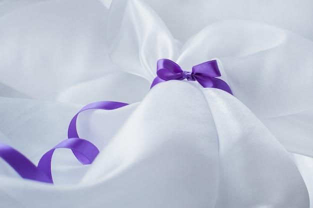 Nastro viola con fiocco su un panno bianco