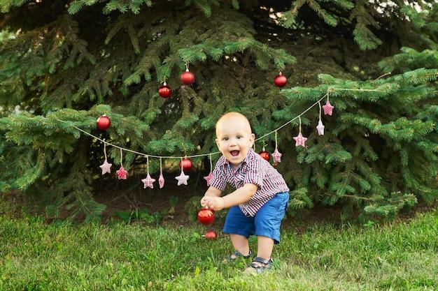 Natale a luglio, bambino a natale. riprese in estate nel parco, decorazioni di capodanno