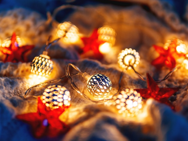 Natale a maglia lampadine e stelle rosse. accoglienti decorazioni natalizie.