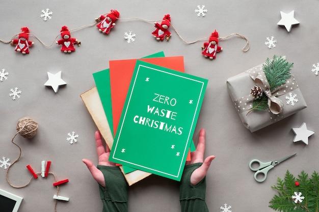 Natale alternativo ecologico. zero rifiuti natalizi, distesi, su fondo di carta artigianale. ghirlanda di bambole in tessuto, mani di donna in possesso di carta di colore rosso e verde con il testo