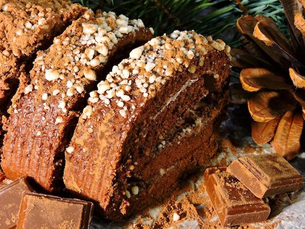 Natale ancora in vita. natale yule log di cioccolato. rami e coni dell'albero di natale. bocconcini di cioccolato.