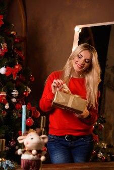 Natale. bella donna sorridente signora sopra l'albero di natale illumina la priorità bassa.