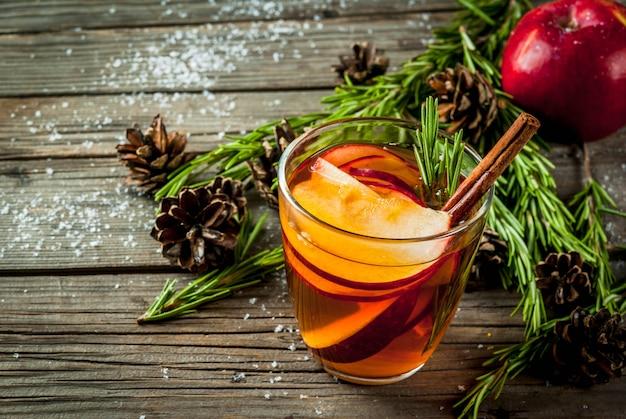 Natale, bevande del ringraziamento. autunno, cocktail invernale grog, sangria calda, vin brulè - mela, rosmarino, cannella, anice. sul vecchio tavolo di legno rustico. con coni, rosmarino. copia spazio