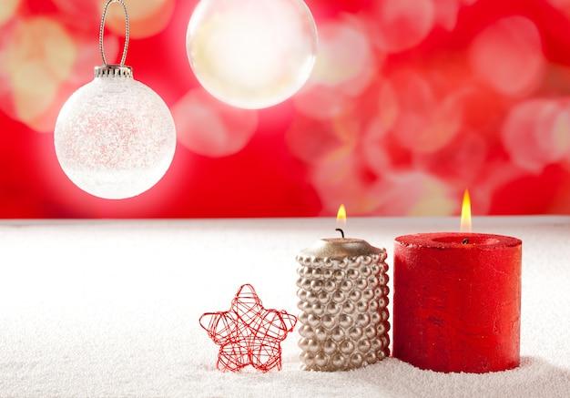 Natale candele rosse d'argento e stelle sulla neve