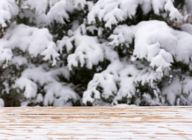 Natale capodanno naturale sfocato sfondo invernale con un tavolo di legno e una zona di montaggio per il posizionamento di oggetti. mock up per testo, congratulazioni, frasi, lettere