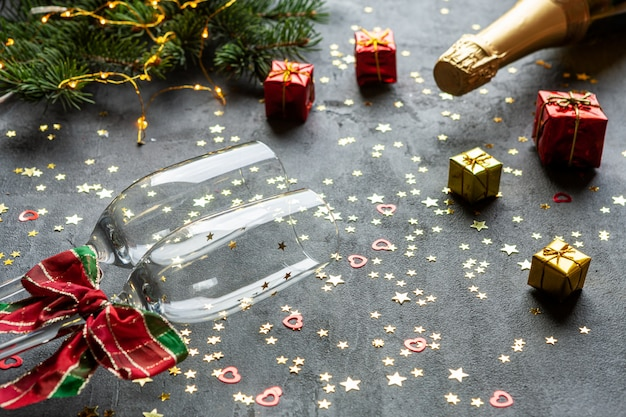 Natale, celebrazione del nuovo anno che serve - piatto a forma di orologio, bottiglie di champagne, due bicchieri di champagne e coriandoli glitter oro,