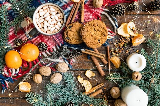 Natale con bevanda calda, biscotti e altri cibi tradizionali e simboli sulla tavola di legno
